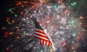 U.S. flag waving in front of fireworks (© AP Images)
